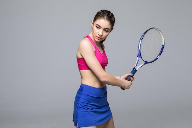 O retrato de um jogador de tênis novo bonito da mulher da aptidão do esporte faz os exercícios isolados.