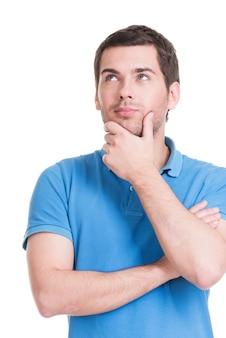 O retrato de um jovem pensante olha para cima com a mão perto do rosto