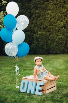 O retrato de um menino bonito com roupas elegantes faz aniversário hoje