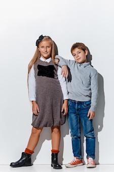 O retrato de um menino bonito e uma menina com roupas jeans elegantes, olhando para a câmera no estúdio