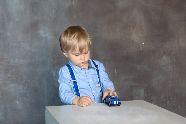O retrato de um menino em uma camisa com suspensórios brinca com carros de brinquedo multicoloridos em casa. um menino brinca com um carro de brinquedo em uma mesa no jardim de infância. o conceito de infância e desenvolvimento infantil