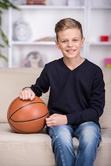 O retrato de um menino está sentando-se no sofá com uma bola.