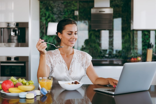 O retrato de uma bela jovem trabalhando com um laptop, enquanto o café da manhã com cereais e leite.