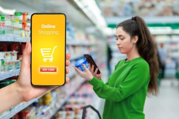 O retrato de uma jovem digitaliza o rótulo do produto com um smartphone e uma mão segura o celular à esquerda