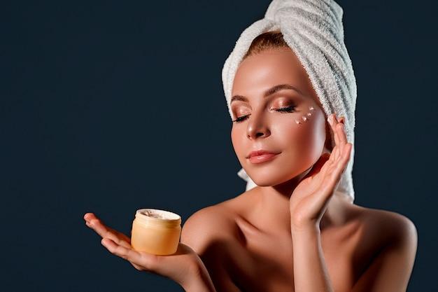 O retrato de uma jovem mulher atraente com uma toalha na cabeça dela usa um creme hidratante para o rosto em uma parede preta.