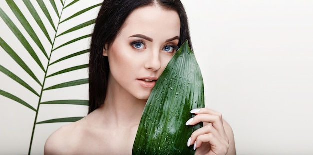 O retrato de uma jovem mulher bonita com a pele lisa saudável prende a folha tropical verde