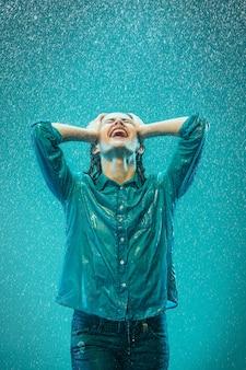 O retrato de uma jovem mulher bonita na chuva