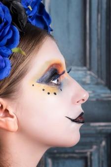 O retrato de uma jovem mulher com o dia das bruxas compõe com as flores azuis.
