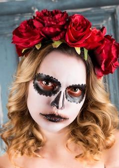 O retrato de uma jovem mulher com o dia das bruxas compõe com as flores vermelhas.