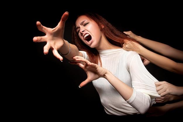 O retrato de uma jovem mulher que, com horror e medo, está tentando escapar das muitas mãos que a puxam para trás e a despedaçam. conceito de solidão, perda, medo. retrato assustador e terrível