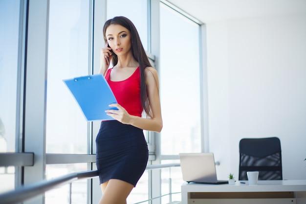 O retrato de uma jovem mulher vestiu-se na posição vermelha na grande janela no escritório moderno claro e no sorriso.