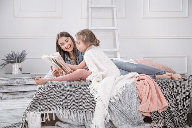 O retrato de uma mãe e de uma filha bonitos novas de sorriso que leem um livro que encontra-se e relaxa na cama em uma sala branca grande brilhante.