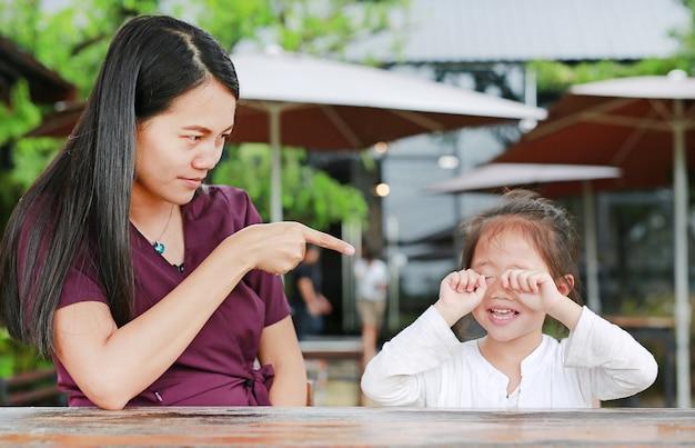 O retrato de uma mãe que discute a sua filha na tabela e sua menina da criança está gritando.
