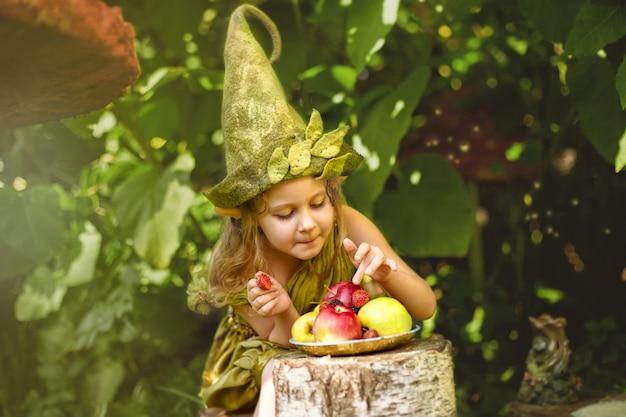 O retrato de uma menina bonita bonito em um gnomo come bagas e maçãs em um prato.