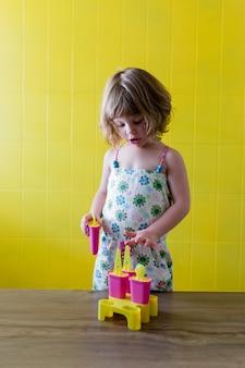 O retrato de uma menina bonita nova da criança que joga com gelado em casa. felicidade e estilo de vida dentro de casa. verão. parede amarela