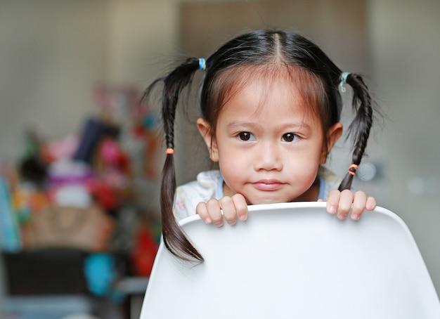 O retrato de uma menina bonito evita na parte de trás da cadeira plástica branca que olha para fora para algo em casa.