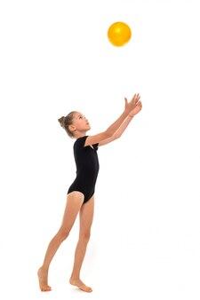 O retrato de uma menina da ginasta na altura completa do trico preto joga a bola amarela acima isolada em um branco