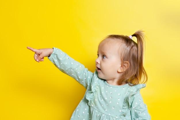 O retrato de uma menina de bebê fofo com olhos azuis em um fundo amarelo aponta para o lado. um lugar para texto.