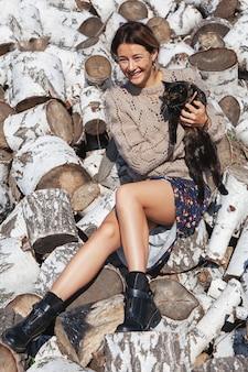 O retrato de uma mulher alegre sorri bonito, segurando um gato preto e senta-se em troncos de bétula.