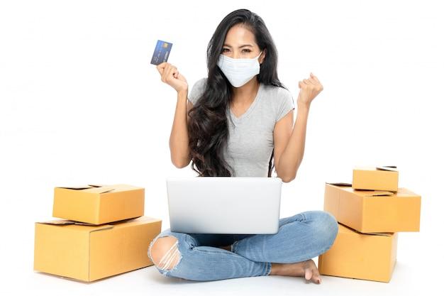 O retrato de uma mulher asiática está sentado no chão com um monte de caixas ao lado. ela tem um cartão de crédito para fazer compras online. ela usa máscara médica contra a gripe. isolado em fundo branco
