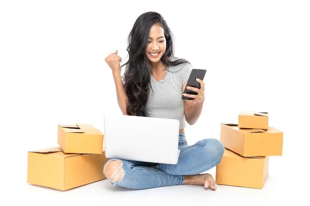 O retrato de uma mulher asiática está sentado no chão com um monte de caixas ao lado. ela usa um laptop e um smartphone para fazer compras online. isolado em fundo branco