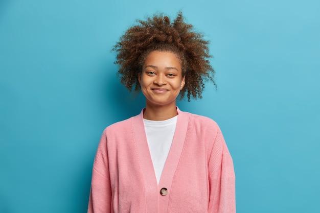 O retrato de uma mulher bonita de pele escura com cabelo afro sorri alegremente vestida com um macacão casual feliz em ouvir as boas notícias.