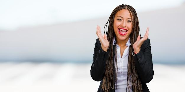 O retrato de uma mulher de negócio preta nova que ri e que tem o divertimento, sendo relaxado e alegre, sente confiável e bem sucedido