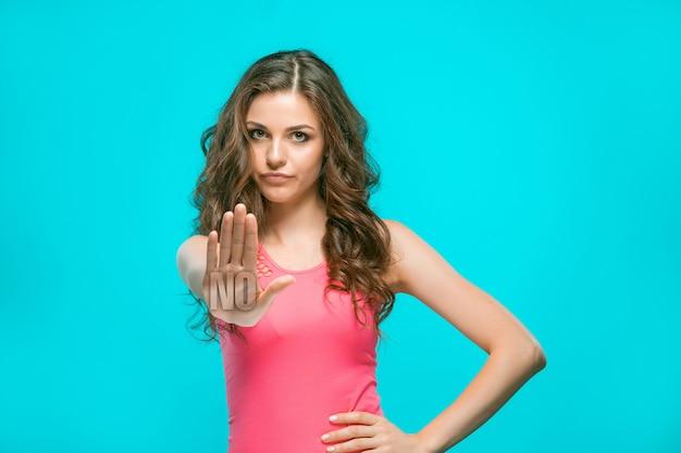 O retrato de uma mulher enojada mostrando não com a mão no azul Foto Premium