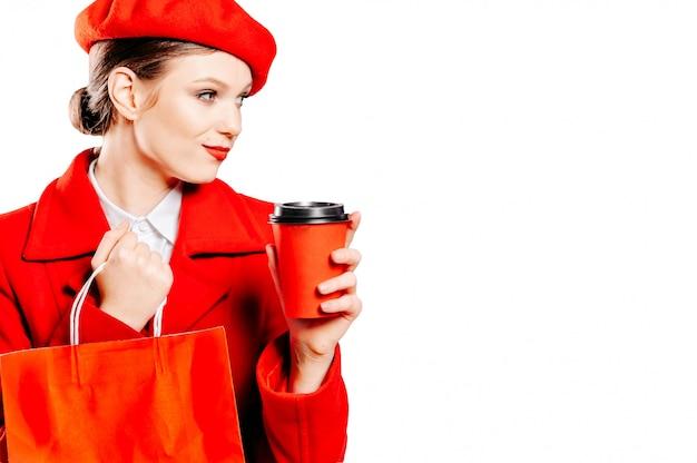 O retrato de uma senhora atrativa elegante elegante bonita atraente em uma boina e um casaco vermelho parece longe bebendo um copo de papel pegar cacau isolado
