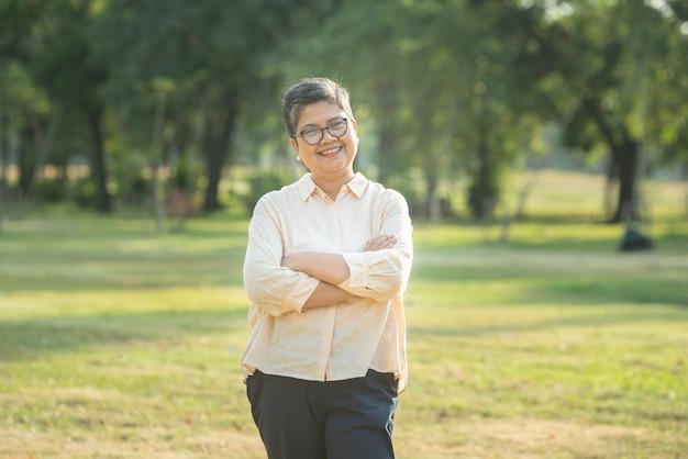 O retrato disparado de feliz, bem sucedido, relaxa a mulher asiática superior caucasiana que sorri com vidros e o olhar despreocupado para a câmera no parque como um fundo com espaço da cópia na luz solar natural do outono.
