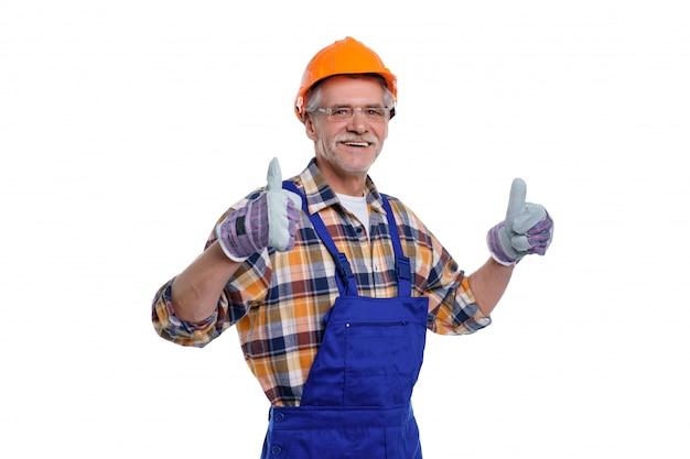 O retrato do arquiteto masculino velho feliz faz sinal bem e sorrindo em branco