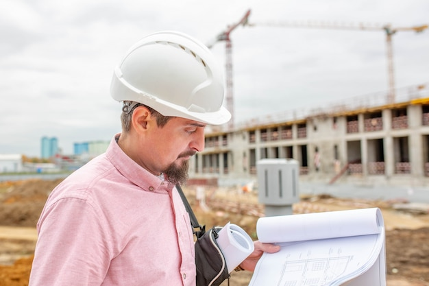 O retrato do arquiteto no trabalho com capacete em um canteiro de obras, lê o plano.