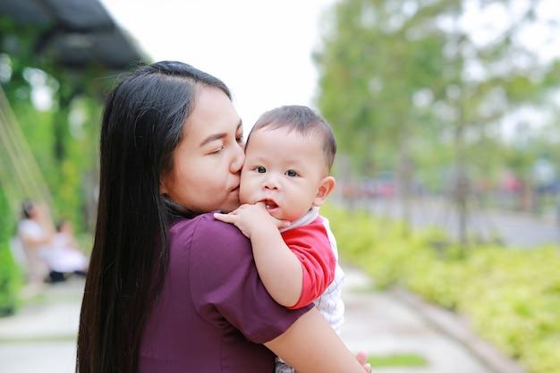 O retrato do bebê infantil está sugando o dedo com levar asiático da mãe.