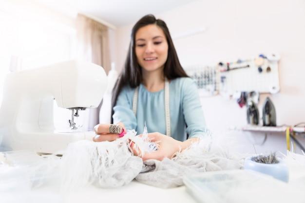 O retrato do close-up da jovem costureira indiana ou costureira costura na máquina de costura em seu próprio local de trabalho.