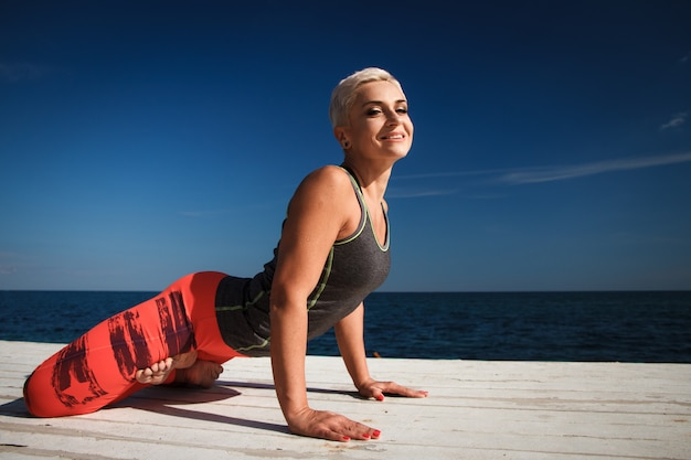 O retrato do close-up da mulher loira adulta com corte de cabelo curto pratica ioga no cais no contexto do mar e céu azul