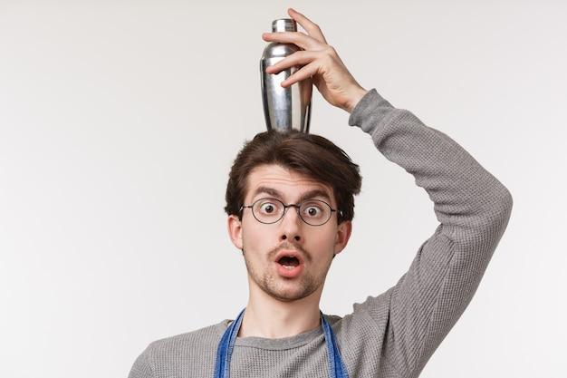 O retrato do close-up do empregado do sexo masculino engraçado, bonito entusiasmado, barman ou barista faz expressão chocada ou surpresa, segurando a coqueteleira na cabeça de equilíbrio,