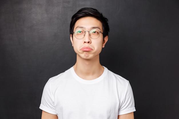 O retrato do close-up do jovem asiático impressionado em t-shirt branca e óculos, olha o canto superior esquerdo com aprovação, dizer não é ruim, apertar os olhos e acenar com a cabeça, aceitando, em pé parede preta