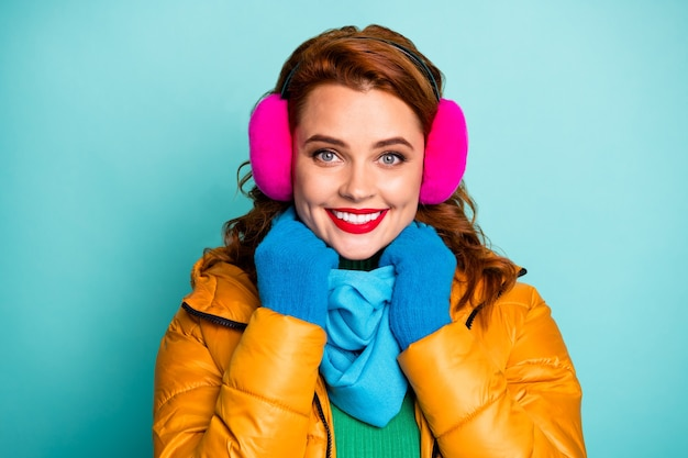 O retrato do close up dos lábios do vermelho da senhora bonita do viajante aproveita o dia de inverno incrível pronto para caminhar usa capas de orelha rosa do lenço azul do sobretudo amarelo casual.