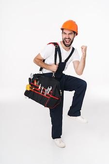 O retrato do construtor de jovem animado positivo no capacete isolado sobre a parede branca segurando o saco com instrumentos de equipamento faz gesto de vencedor.