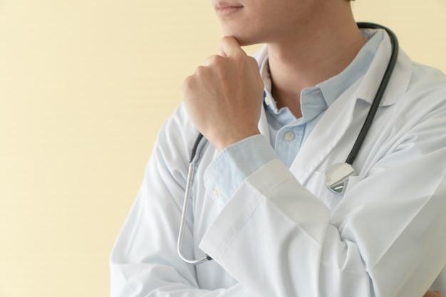 O retrato do doutor novo asiático com braços cruzou guardar o estetoscópio no regaço da emergência do hospital. conceito de estilo de vida do paciente de saúde e médico.