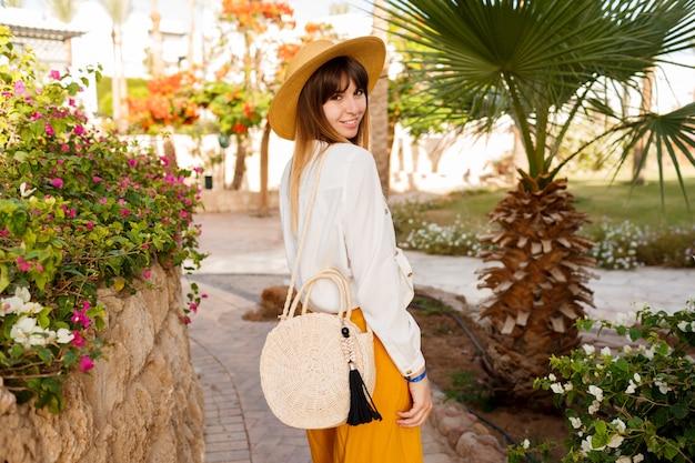 O retrato do estilo de vida da mulher bonita caucasiana no chapéu de palha, blusa branca e saco de estilo bali andando no jardim tropical.