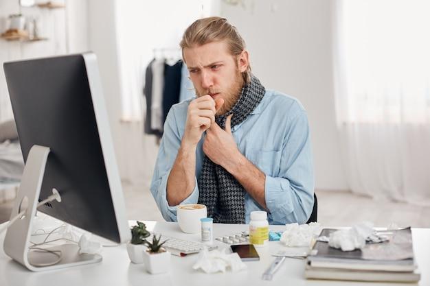 O retrato do gerente masculino barbudo doente doente tosse, tem frio e gripe. jovem de cabelos louro tem coriza, tosse e resfriado, senta-se no local de trabalho na frente da tela do computador. doença e infecção
