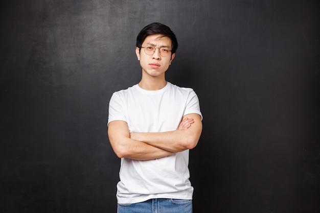 O retrato do homem asiático asiático de aparência séria confiante nos vidros, estrabismo cauteloso e descrença, cruza as mãos sobre o peito, não confia na pessoa que fala, parede preta