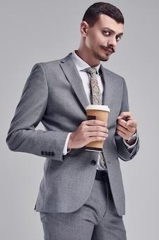 O retrato do homem de negócios árabe seguro novo considerável com bigode extravagante no terno completo cinzento da forma prende uma xícara de café em suas mãos no estúdio.