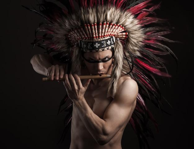 O retrato do homem forte indiano que levanta com nativo americano tradicional compõe. tocando flauta