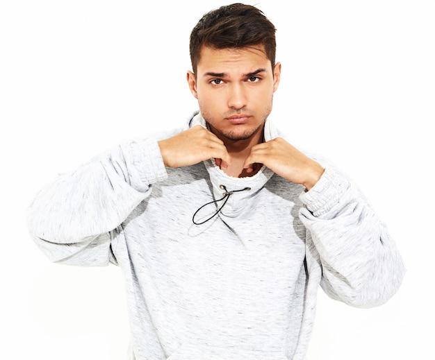 O retrato do homem modelo considerável novo vestiu-se na roupa ocasional cinzenta do hoodie que levanta na parede branca. isolado