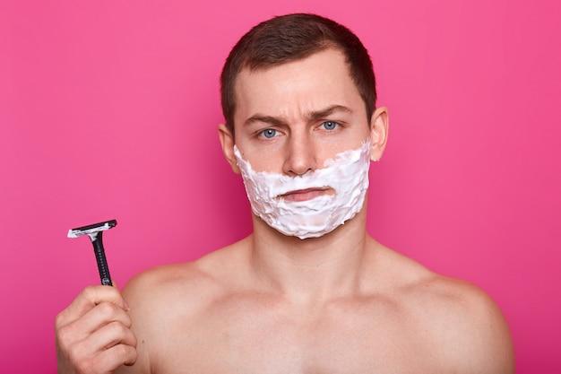 O retrato do homem novo atlético considerável chateado levanta sobre a parede cor-de-rosa brilhante no estúdio, parece insatisfeito por causa da qualidade da lâmina e do processo de barbear. conceito de cuidado e masculinidade.