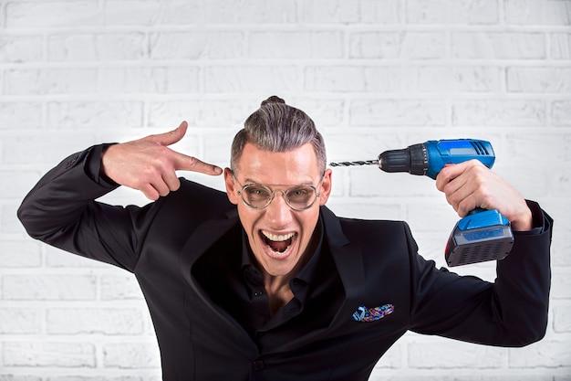 O retrato do homem novo engraçado louco no terno preto que sorri na câmera com uma broca guarda em seu templo. estúdio indoor tiro. foda-se o cérebro