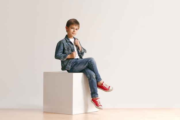 O retrato do menino bonitinho com roupas jeans elegantes, olhando para a câmera contra a parede branca do estúdio. conceito de moda infantil