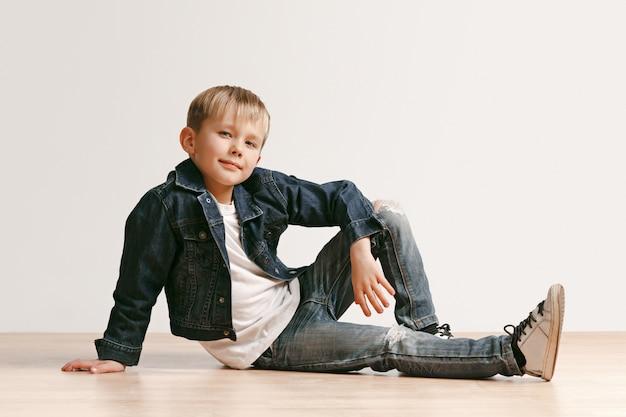 O retrato do menino bonito da criança na roupa à moda das calças de brim que olha a câmera contra a parede branca do estúdio.